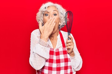 Senior grey-haired woman wearing apron holding whisk covering mouth with hand, shocked and afraid...