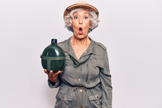 Senior grey-haired woman wearing explorer hat holding water canteen scared and amazed with open mouth for surprise, disbelief face