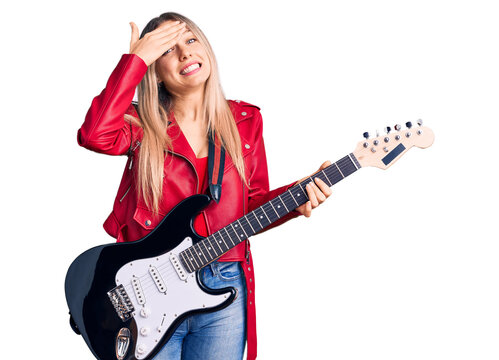Young beautiful blonde woman playing electric guitar stressed and frustrated with hand on head, surprised and angry face