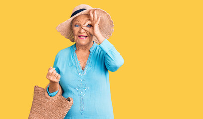 Senior beautiful woman with blue eyes and grey hair wearing fashion dress and hat holding summer wicker handbag smiling happy doing ok sign with hand on eye looking through fingers