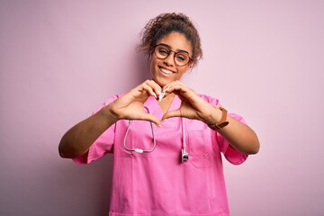 African american nurse girl wearing medical uniform and stethoscope over pink background smiling in...
