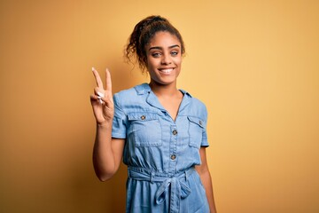 Young beautiful african american girl wearing denim dress standing over yellow background smiling...