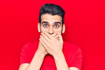 Young handsome man with beard wearing casual t-shirt shocked covering mouth with hands for mistake....