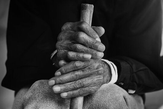Asian old man sitting with his hands on a walking stick.