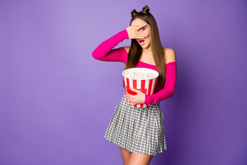 Photo of terrified lady two buns closing eyes hold popcorn bucket watch horror movie wear pink off-shoulders cropped top plaid short skirt isolated pastel purple color background