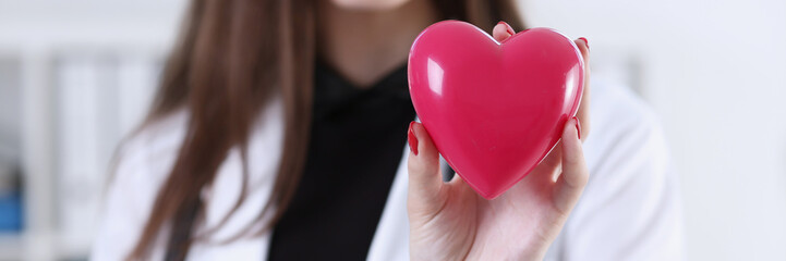 Female medicine doctor hands holding and covering red toy heart closeup. Cardio therapeutist,...