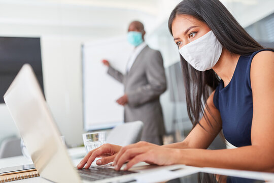 Businesswoman with face mask works on laptop