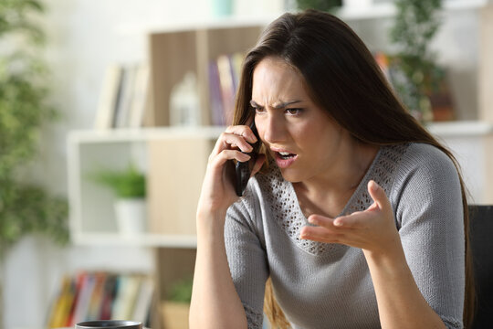 Angry woman calling arguing on phone at home