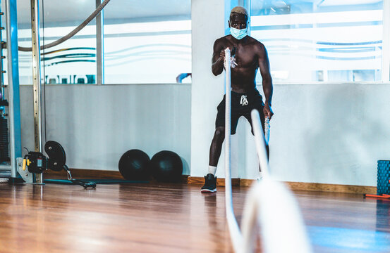 Young black man doing workout session with battle rope while wearing face mask for coronavirus prevention - Healthcare, fitness and sport concept - Focus on face