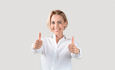 Cheerful business lady showing thumbs up gesture on light background