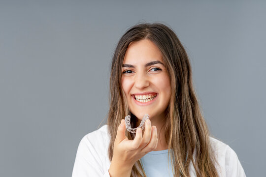 Beautiful smiling Turkish woman is holding an invisalign bracer in a grey background studio with copy space