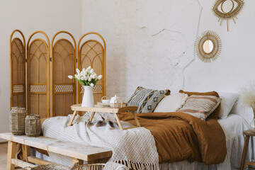 Comfort bedroom in boho style interior with lovely furnishing
