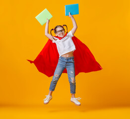 Little superhero jumping with notebooks.