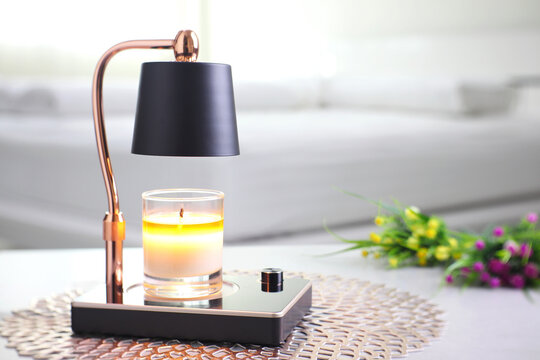 The luxury lighting aromatic scent  glass candle is put on the electric lamp candle warmer heater on the grey table in the white bedroom to create relax and romantic ambient