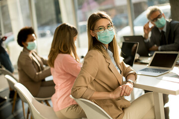 Young woman with group of business people have a meeting and working in office and wear mask as protection from corona virus