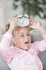 Cute little emotional girl with alarm clock.
