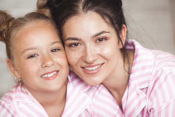 Attracive young mother and her little daughter in the bedroom.