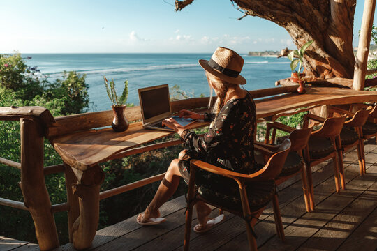 Freelance concept. Pretty young woman using laptop in cafe on tropical beach in outdoor cafe terrace with sea view. Work and travel