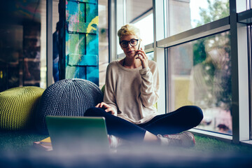 Portrait of young hipster girl talking on mobile while working on freelance in loft interior...