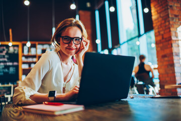 Portrait of successful businesswoman using laptop for distance job sitting in cafe with wifi, attractive female freelancer enjoying  free working schedule looking at camera uploading software Wall mural