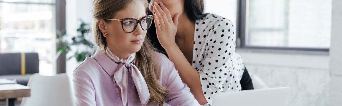 website header of businesswoman whispering in ear of coworker in glasses while gossiping in office