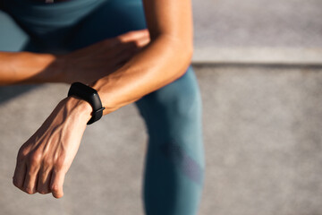 Hands of young woman with sports watch