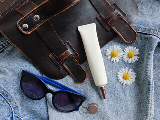 Cosmetic tube with long nozzle and bronze screw cap. Mock-up. Jeans background with handbag, sunglasses, camomiles, silver earrings. Face and eye cream squeeze. Top view. Natural organic spa cosmetic