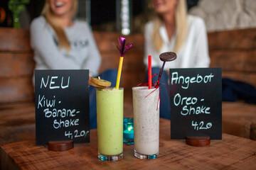 Angebot-Schilder Shakes in einer Bar mit Gästen
