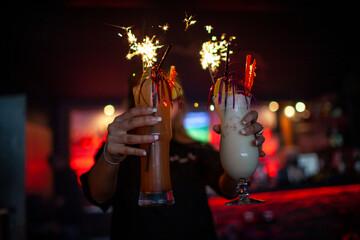 Cocktails mit Wunderkerzen in einer dunklen Bar