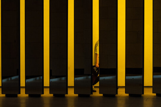 Row Of Illuminated Yellow Columns With A Fleeting Silhouette In One Of Them.