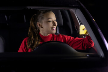 smiling long hair girl in car driving at night makes selfies shares photos in social networks, uses free internet connection. safe driving concept. social media concept Photographed on mobile phone.