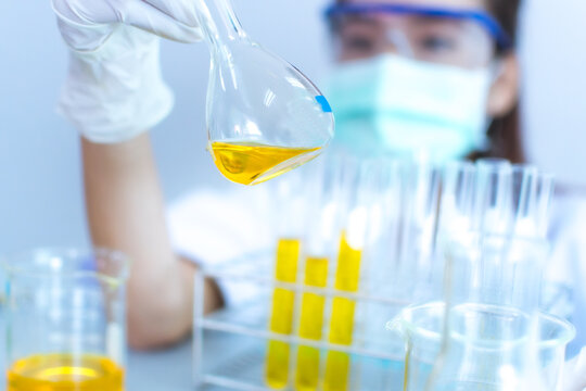 Scientist Examining Yellow Chemical In Laboratory