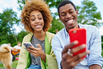 Positive african american friends with funny grimaces on face looking at front camera of modern smartphone and making selfie photos for blog spending together free time in urban setting