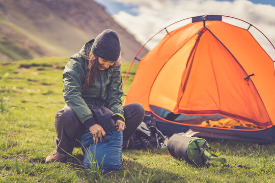 alpine woman folding sleeping bag and other accessories for camping. In the background orange tent and equipment for outdoor activities.