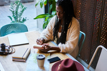 Creative afro american female concentrated writer dressed in trendy casual outfit working on new...