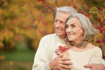 Beautiful senior couple hugging in the park with rowan berries