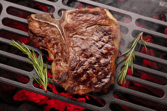 T-bone beef steak cooking on grill