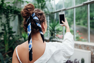 Young woman taking selfie walking in tropical greenhouse using smartphone. Girl wearing scarf in hair