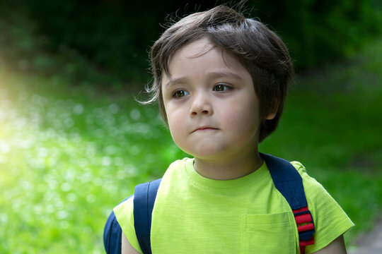 Portrait of 4 years old boy standing alone and looking out with blurry background of green forest, Excited kid carrying backpack get ready to go to for adventure with school summer camp