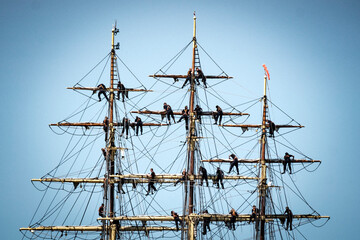 Low Angle View Of People On Sailboat Masts Against Clear Sky