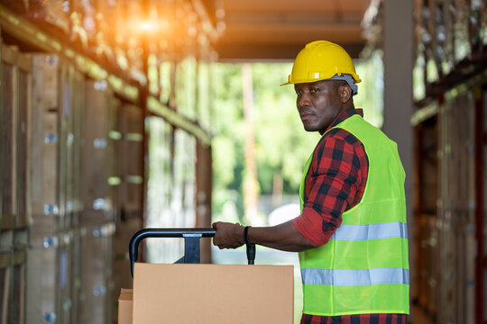Warehouse worker loading or unloading boxes at warehouse.