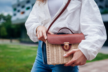 Close-up of stylish female straw handbag. Young woman wearing outfit and accessories outdoors. Summer purse