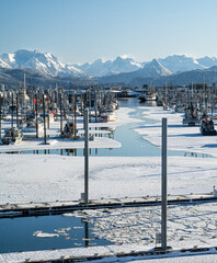 Mostly icy view down boat channel in Homer Alaskas small boat harbor