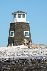 Lighthouse behind frozen beach covered in wooden shingles.psd