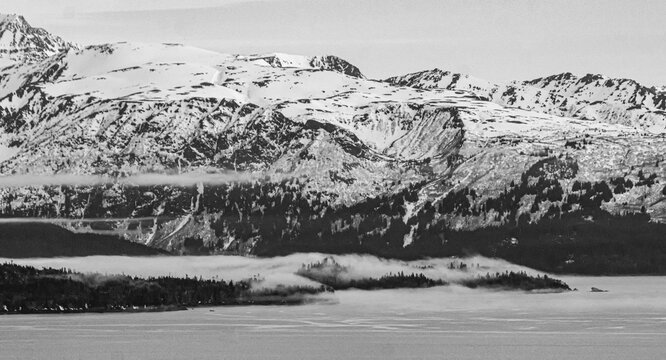 Fog seeps out of fjord valley and out on ocean bay with snowy mountains in the background