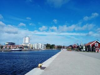 Fototapeta Buildings By Street Against Blue Sky obraz
