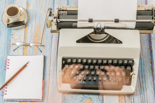 Antique typewriter with a notebook and pen with fuzzy hands