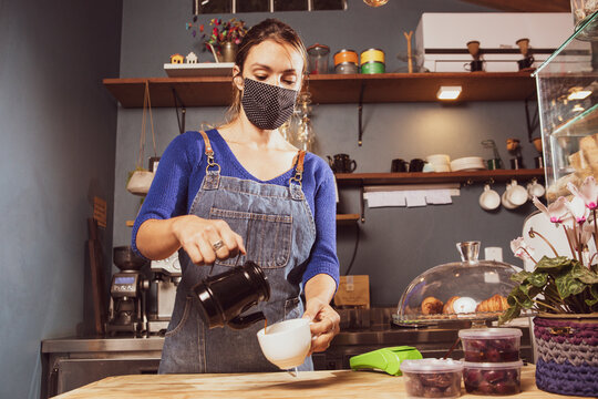 Caucasian woman serving coffee in a small business wearing mask durind covid-19 pandemic reopening after quarantine
