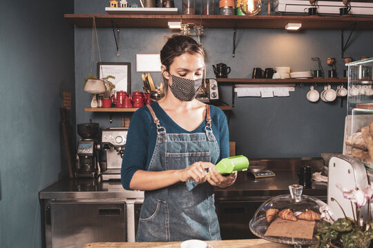 Caucasian woman handling card payment method in a small bakery business wearing mask durind covid-19 pandemic reopening after quarantine