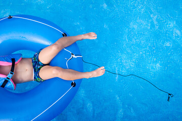 Boy bathing in a pool playing with a large round float.